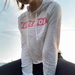 "Vit med rosa text ""superior"" cropped hoodie. Använts en gång. Frakt ingår inte."