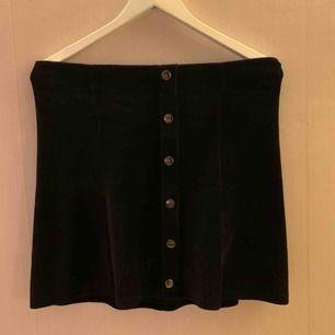 Svart ribbad kjol med fusk knappar från gina tricot. Manchester imitation. Kjolen innehåller 3% elastan.   Kan mötas upp i Borås, eventuellt Göteborg, annars står köparen för frakten.