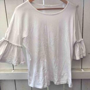 Säljer en basic fin vit tröja med volangärmar, använd endast en gång.