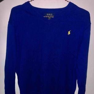 En tröja från Ralph Lauren i en fin blå färg, med en fin v-ringning. Det står XL som storlek på lappen men det är en M/L. Tröjan är till både tjejer och killar. Nypriset är 999kr. Tröjan är inte använd speciellt mycket.