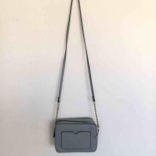 Blå/grå väska med silvriga detaljer. Använd fåtal gånger. En fläck finns inne i väskan som visas på bild 3