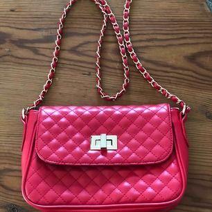 Klarröd väska från Asos. Mått ca 25x18.  Lite repigt på spännet (se bild 3) annars i fint skick.  Kan mötas upp i Stockholm eller skicka (fraktkostnad tillkommer) 👜