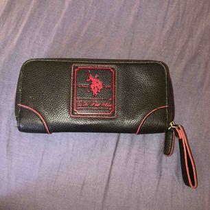 En skit snygg svart polo Ralph Lauren plånbok med röda detaljer! Många stora fack, finns även hållare till kort och mynt + även sedlar! Har aldrig använt den då jag har andra plånböcker. Ny pris 500kr, säljer för 70+ frakt! ÄKTA!!!