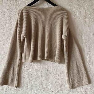 Stickad tröja i croppad modell, slutar på början av höfterna skulle jag säga. Frakt tillkommer