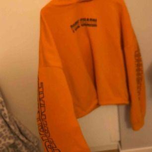 Orange hoodie från hm med tryck på framsidan och på armarna