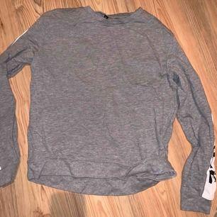 """Grå långärmad tröja med tryck på ärmarna """"nerver miss a chance"""""""