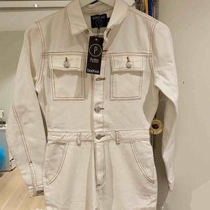 En jättefin vit jeans byxdress från boohoo (petit) säljer pågrund av att den är för liten. Oanvänd och alla lappar sitter kvar.