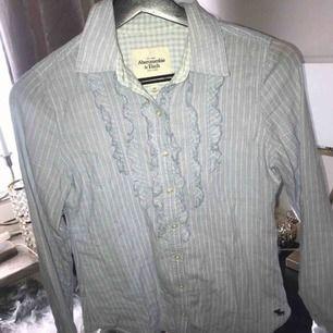 Ljusblå randig skjorta/blus från Abercrombie :) Söta volanger framtill. Fraktkostnad tillkommer