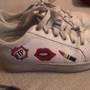 Ett par vita sneakers med röda motiv på sidan. Köptes i Portugal på påsklovet och är använda ett fåtal gånger. Vet tyvärr inte vad märket på skorna heter, då de var någon skobutik i Portugal. Pris kan diskuteras. Strl 38