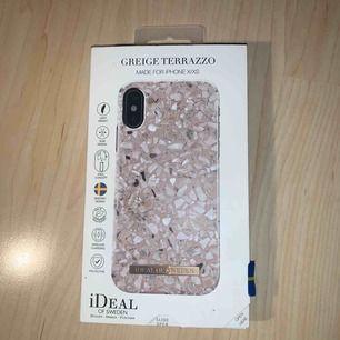 """Säljer ett superfint, oanvänt (endast provat) mobilskal från Ideal of Sweden. Skalet passar till IPhone X och IPhone XS och det säljes p.g.a att jag råkade köpa fel storlek. Färgen är ljusrosa och motivet heter """"Greige Terrazzo"""". Frakt ingår i priset!"""