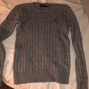Frakt ingår inte! En grå kabelstickad Ralph lauren tröja i fullt skick även fast den är några år gammal.