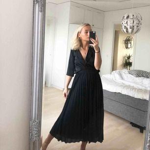 Plisserad kjol i svart, två lager. Bra skick! Inköpt för 399.