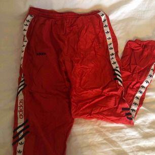 """röda adidas byxor i """"prassel"""" material, med vit rand och adidas logo längs båda benen. Stretchig resår så passar allt från storlek S till L"""