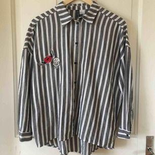 """Grå-vit-randig skjorta med två patches på framsidan. Broderad text """"authentic"""" på baksidan. Aldrig använd och i mycket gott skick. Köpare står för frakt!"""