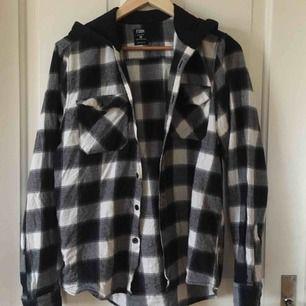 Svartvit flanellskjorta med huva. Medel-använd men i gott skick utan fläckar och skador. Köpare står för frakt!