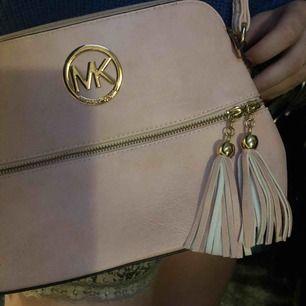 Fejk Michael Kors väska. Väskan köpte jag för 450 kr. Den är som i nyskick, har inte använts. Färg:Smutsrosa. Vill du veta mer så är det bara att kontakta!  Har inget kvitto. Står inte för leveransen