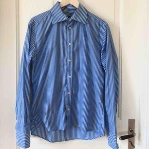Blåvit-randig skjorta med vita knappar. Använd men i bra skick. Köpare står för frakt!