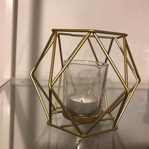 En jättefin ljushållare som är guldfärgad. Man lägger i egna värmeljus i glaset