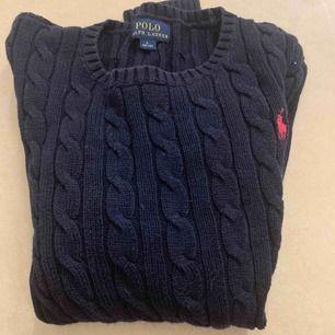 En fin kabelstickad marinblå tröja från Ralph lauren den är i barn L så kanske i storlek 140-160