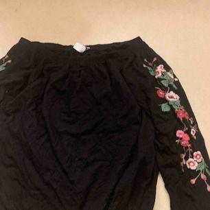 En svart långärmad top med blommor på armarna