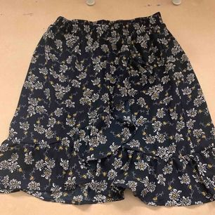 En söt omlott kjol mörkblå med blommor perfekt till vår, sommar eller höst