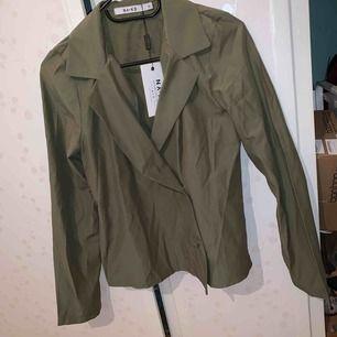 Söt olivgrön skjorta/blus i luftigt och tunt material. Oanvänd