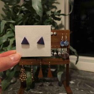 Handgjorda örhängen av lera, formade till trianglar.