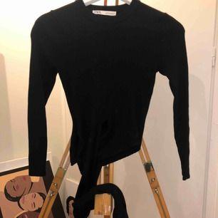 Cool svart tröja med knytning runt midjan. Framhäver ens former väldigt fint. Ribbat tyg i fint skick. Köpt på Zara. Tröjan är i storlek M men skulle säga att den passar s om inte till och med xs