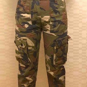 Militärinspirerade byxor. Är lite kortare i benen och har resårband längst ned som man kan se på bild 2. Går att justera hur den sitter runt midjan med banden som syns på bild 3. Är mid high. (Färgerna stämmer som bäst med verkligheten på bild 3)