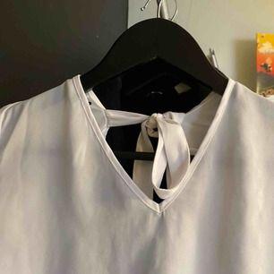 luftig vit blus från na-kd med knytning i nacken och trumpetärmar. superfin men knappt använd. pm för mer info/bilder.