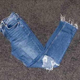 Jeansfärgade jeans från Gina Tricot i strl 36. De har ett hål på ena knät och fransiga byxben vilket gör att de ser lite våriga ut. Pris kan diskuteras och det är först till kvarn som gäller.