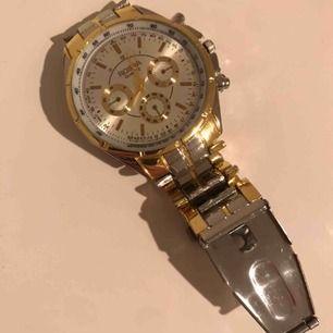 En jätte fin klocka i märket ROSRA. Den är guld och silver. Inga repor eller sådant, i fint skick och batteriet funkar. Passar både dam och herr.