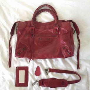 """Balenciaga-väska i modellen city och färgen """"rouge vif"""". 100% äkta, spegel, axelrem och läderbit medföljer. Fint använt skick, inga defekter. Nypris var ca 20 800, men denna modell & färgkombination säljs inte längre. Hör av er för fler bilder! ❤️❤️"""