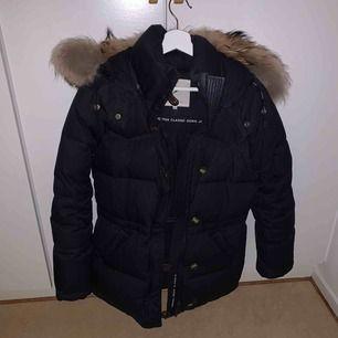 Boomerang Alexandra Down jacket. I färgen blackish navy alltså mörk/marinblå. Superfin och skön vinterjacka framförallt väldigt varm och bra. Bra skick, lite smink på kragen men det går att tvätta bort. Pälsen ingår ej.