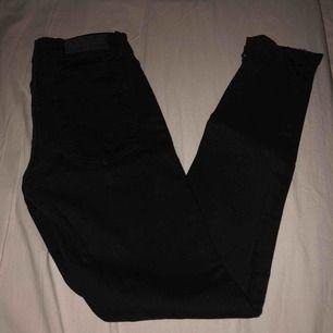Jeans med hål på ena knäet och riped vid slutet av byxorna, nästan helt oanvända