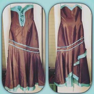 Helt ny balklänning, aldrig använd 🌸  Brunt och turkos 👗 Uppskattar stl till en 38/40  Dragkedja + snörning i ryggen så man kan justera storleken  Pärlorna på klänningen finns inte på längre.  Priset kan diskuteras vid snabb affär