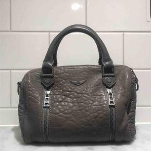 """Säljer denna snygga Zadig Voltaire väska i modellen """"sunny xsmall"""". Köptes för 1,5 år sedan för 3500kr. Säljes för 1700kr! Så passa på!☠️ Den är i en mörkgrå färg och är i toppskick. Måtten är 23cm x 14cm. (Pris kan diskuteras!)"""