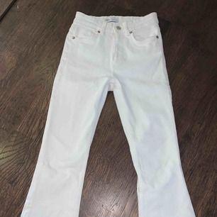 Säljer vita byxor med lite utsvängda ben och slitningar längst ner.