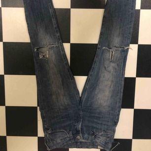Begagnade byxor ifrån Lee, har dessa triangel formade hålen på knäna som är populärt just nu. Bält hålen är avdragna.