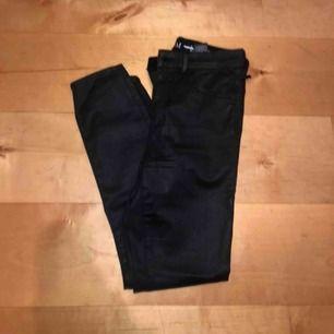 Helt oanvända jeans/byxor i nästan lack och skinn material, strl M men kan själv också ha S. Skriv för bild på, köparen står för ev frakt