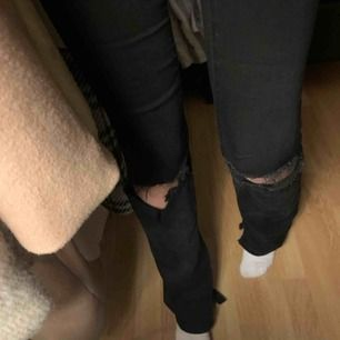 Långa jeans med slitningar vid knäna och liten slits vid slutet av benen