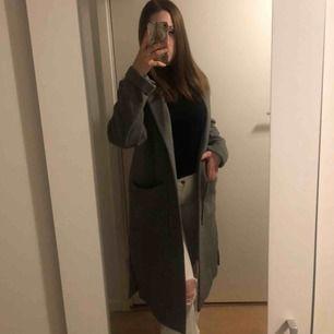 Lång grå kappa med slits på varje sida. Köpt från H&M. Kan mötas upp i Stockholm annars tillkommer frakt!