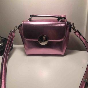 Liten rosa väska med avtagbart axelband, använd fåtal gånger i nyskick. Har två små innerfickor. Är ca 20cm bred och 15cm hög (man får plats med de allra nödvändigaste) kan mötas upp eller frakta, köpare står för frakt