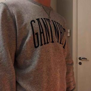 GANT sweatshirt i grått med marinblått tryck, sparsamt använd. Inga hål eller slitningar, sitter snyggt!