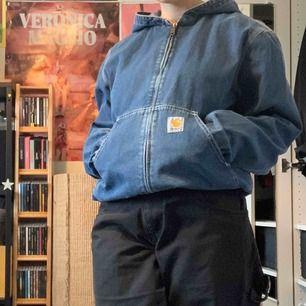 Vintage Carhartt jeansjacka köpt på secondhand, mycket bra skick saknar dock snöret från luvan, säljer pga att den inte kommer till användning