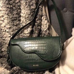Skitsnygg mörkgrön väska från Nakd. Rymlig, lätt att stänga och reglerbart band.