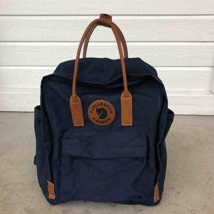 Helt ny ryggsäck från Fjällräven Kånken, aldrig använd. Väskan är i mjukt marinblått tyg och handtagen är i brunt skinn.   Superfin och tidlös!  Kan skicka mot att köparen betalar frakt