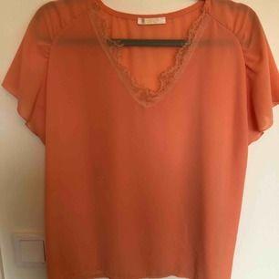 Jättefin orange blus från Mirelle. Känns lyxig och sval mot huden. Perfekt till vår och sommar.  Köparen står för frakten.