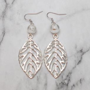 Fina silverfärgade örhängen med tvåfärgade glaspärlor och stora löv. Nickelfria. Fri frakt vid köp över 100:-.