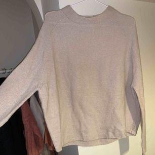 Stickad tröja från Wera i storlek S. Den är ljusbeige och har en halvhög krage. Aldrig använd